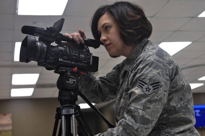 U.S. Air Force Senior Airman Megan Reed, 17th Training Wing Public Affairs broadcast journalist, gathers b-roll of the grand opening of a coffee shop on Goodfellow Air Force Base, Texas, January 13, 2016. The Public Affairs office covers events happening on or off base that impact Godfellow. (U.S. Air Force photo by 2nd Lt. Tisha Wilkerson/Released)