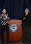 Alicia Borlik and Tina Carlsen, instructors for the online version of the Basic Affairs Specialist Course at the Defense Information School on Fort Meade, Md., stand by the DINFOS seal in the school's graduation room Jan. 10, 2017. Basic Public Affairs Specialist Course-Advanced Distributed Learning provides a low-cost alternative to the three-month resident course.