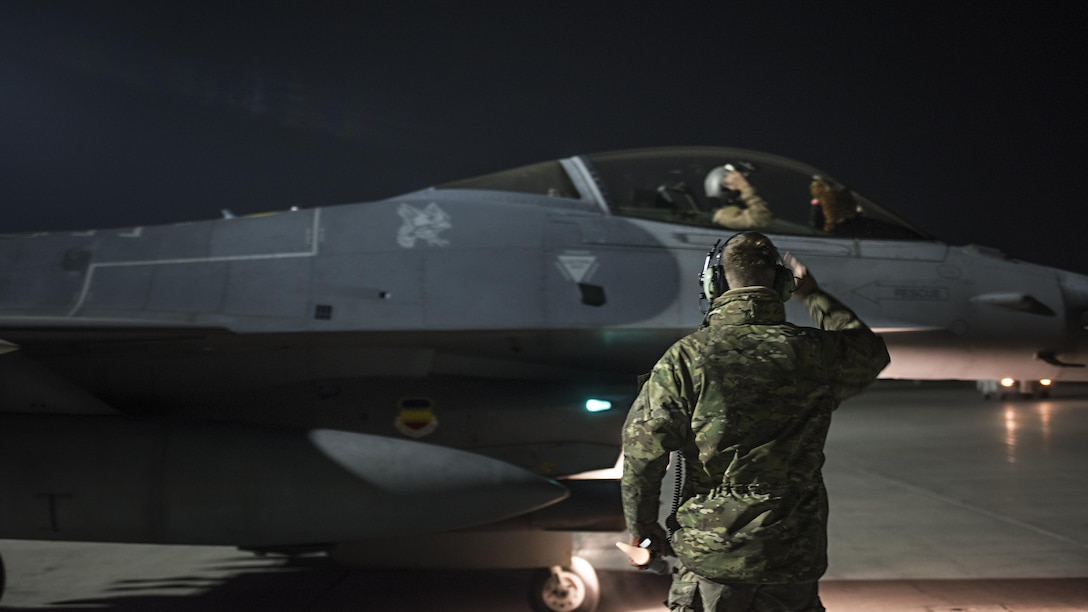 Capt. David, 79th Expeditionary Fighter Squadron pilot, and Staff Sgt. Daniel Lasal, 455th Expeditionary Aircraft Maintenance Squadron dedicated crew chief, salute one another before a night mission Jan. 13, 2017 at Bagram Airfield, Afghanistan. David enlisted in the Air Force in 2004 as an F-16 Fighting Falcon avionics specialist and now flies the same airframe he used to be a maintainer for. (U.S. Air Force photo by Staff Sgt. Katherine Spessa)