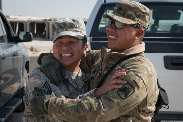U.S. Air Force Tech. Sgt. Mary Jane Palumbo, 134th Expeditionary Fighter Squadron aviation resource manager, and her brother, U.S. Army Staff Sgt. Quincy Mora, AH-64 Apache mechanic, embrace one another as they meet for the first time in ten years Jan. 7, 2017. The siblings are both deployed in support of Operation Inherent Resolve. (U.S. Air Force photo/Master Sgt. Benjamin Wilson)(Released)