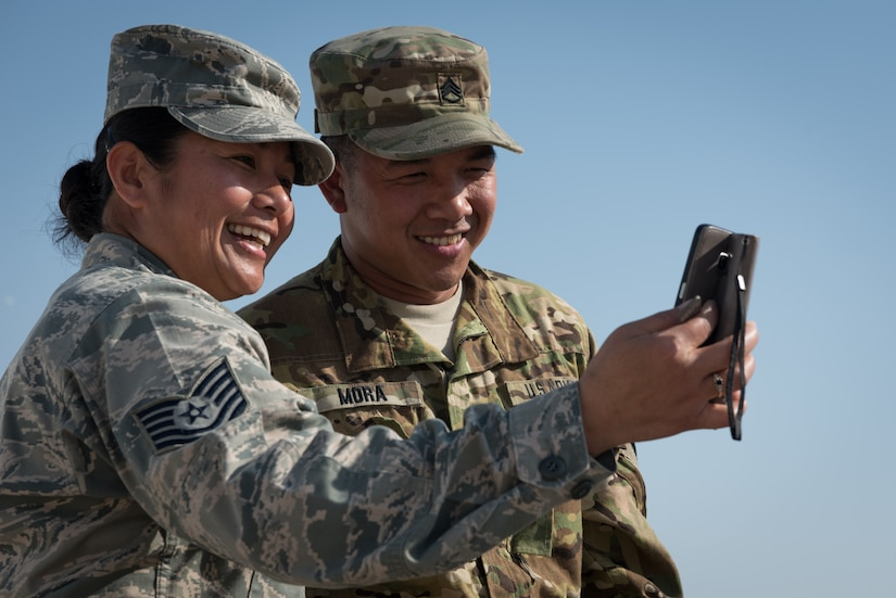 Air Force Tech. Sgt. Mary Jane Palumbo and her brother, Army Staff Sgt. Quincy Mora, video chat with their family while deployed, Jan. 7, 2017. The siblings are originally from the Federated States of Micronesia and had not seen each other in ten years. Air Force photo by Master Sgt. Benjamin Wilson