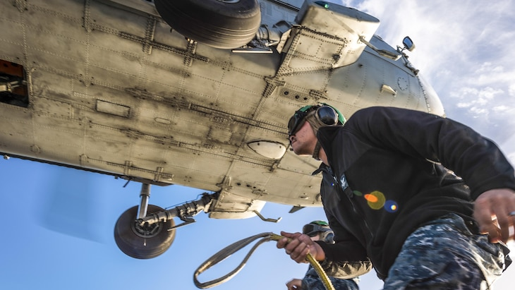 Navy Petty Officer 2nd Class Jason Lee attaches a recovery device to an MH-60S Seahawk helicopter at San Clemente Island, Calif., Jan. 11, 2017. Navy photo by Petty Officer 2nd Class Chad M. Butler