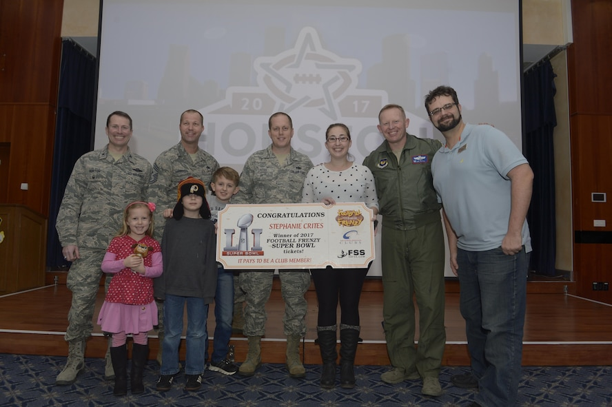 U.S. Air Force Staff Sgt. Richard Crites, 52nd Maintenance Squadron senior munitions inspector, with his family are presented with the grand prize from the Football Frenzy contest by 52nd Fighter Wing leadership and 52nd Force Support Squadron at Club Eifel on Spangdahlem Air Base, Germany, Jan. 10, 2017. The grand prize is two tickets to Super Bowl LI with airfare and hotel. (U.S. Air Force photo
