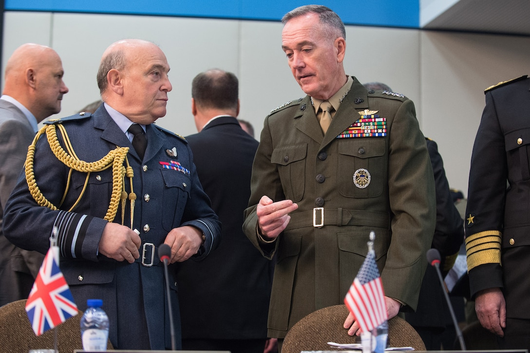 Marine Corps Gen. Joe Dunford, chairman of the Joint Chiefs of Staff, speaks with Air Chief Marshal Sir Stuart Peach, British defense chief, before a NATO meeting.