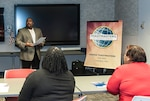 DLA Land and Maritime EEO Specialist Michael McCoy speaks during a Toastmaster International Club 3500 meeting inside the operations center at Defense Supply Center Columbus. A.G.O.I.S.S.I. (A Group Of Individuals Seeking Self Improvement) leads its district with the most consecutive years achieving 10 out of 10 annual goals set forth by the organization.