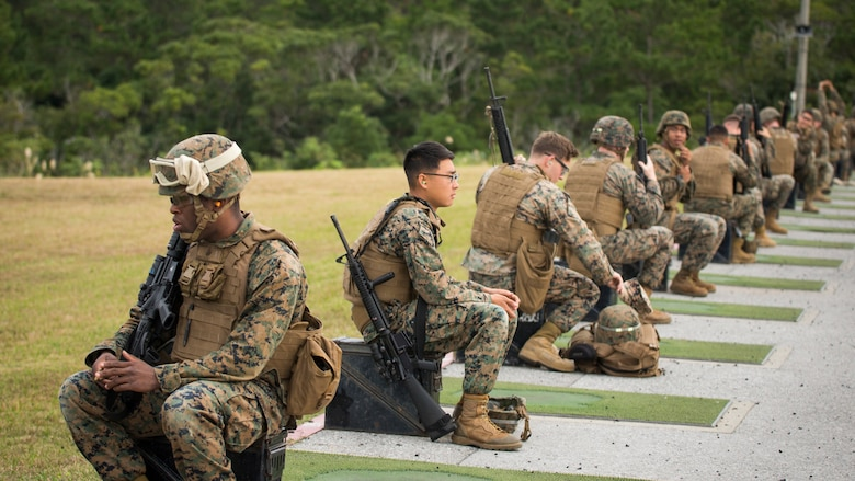 Marines from various units within Okinawa prepare for their turn to fire the table two portion of the annual rifle range qualification, Jan. 12, 2017, at Camp Hansen, Okinawa, Japan.  The Marine Corps revised table two of the marksmanship program October 2016 to increase marksmanship skill and realism in a combat environment. The Corps requires Marines to annually qualify at the range to determine their marksmanship skill.