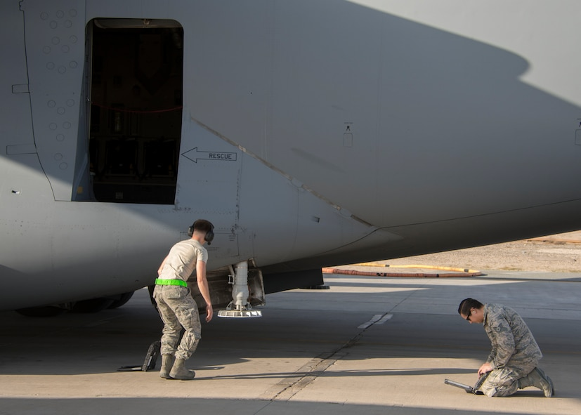 Airman 1st Class Nathan Travis, an aircraft electrical and environment systems journeyman, left, and Staff Sgt. Bradley Chaplin, an aerospace maintenance craftsman, right, both from the 5th Expeditionary Air Mobility Squadron, begin a post-flight inspection of a C-17 Globemaster III at an undisclosed location in Southwest Asia Jan. 13, 2017.  The 5th EAMS consists of 65 maintenance personnel. (U.S. Air Force photo/Senior Airman Andrew Park)