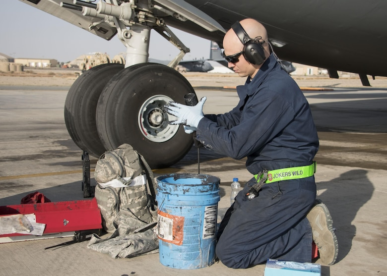 Tech. Sgt. Devon Edwards, a 5th Expeditionary Air Mobility Squadron aerospace maintenance craftsman, fills a grease gun at an undisclosed location in Southwest Asia Jan. 13, 2017. During post-flight inspections of the C-17 Globemaster IIIs, 5th EAMS Airmen grease approximately 200 points around the aircraft. (U.S. Air Force photo/Senior Airman Andrew Park)