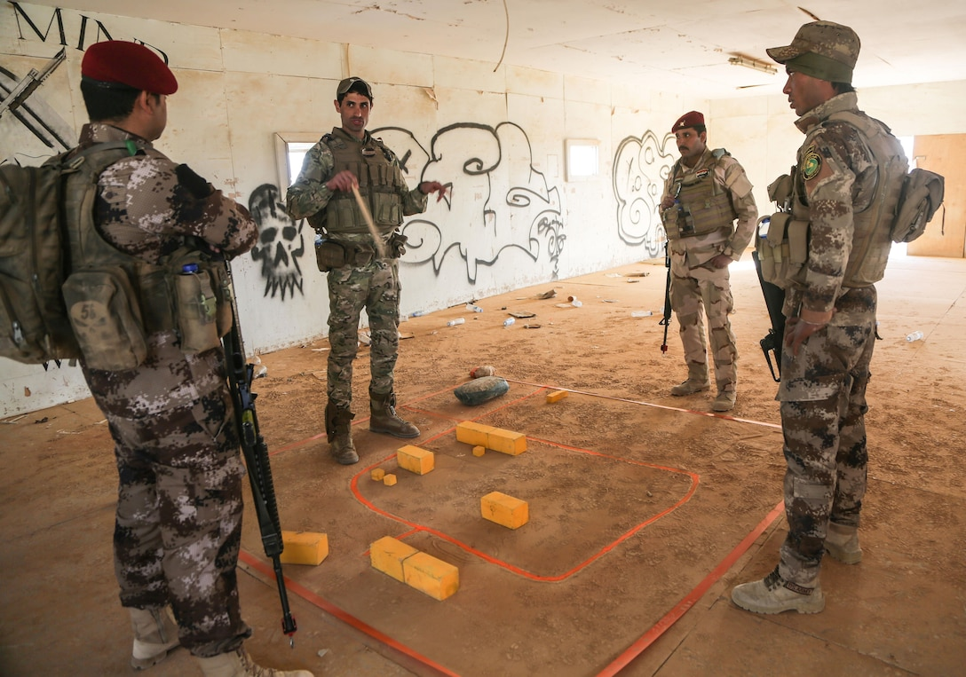 An Iraqi platoon commander, center, discusses scheme of maneuver to his squad leaders, all from 7th Iraqi Army Division, during assault movement training at Al Asad Air Base, Iraq, Jan. 13, 2017. Training at building partner capacity sites is an integral part of Combined Joint Task Force – Operation Inherent Resolve's global Coalition effort to train Iraqi security forces personnel to defeat ISIL. CJTF-OIR is the global Coalition to defeat ISIL in Iraq and Syria. (U.S. Army photo by Sgt. Lisa Soy)