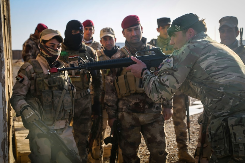 "A British trainer, from 4th Battalion, ""The Rifles,"" shows Iraqi soldiers from 7th Iraqi Army Division how to hold a rifle during assault movement training at Al Asad Air Base, Iraq, Jan. 13, 2017. Training at building partner capacity sites is an integral part of Combined Joint Task Force – Operation Inherent Resolve's effort to train Iraqi security forces personnel to defeat ISIL. CJTF-OIR is the global Coalition to defeat ISIL in Iraq and Syria. (U.S. Army photo by Sgt. Lisa Soy)"