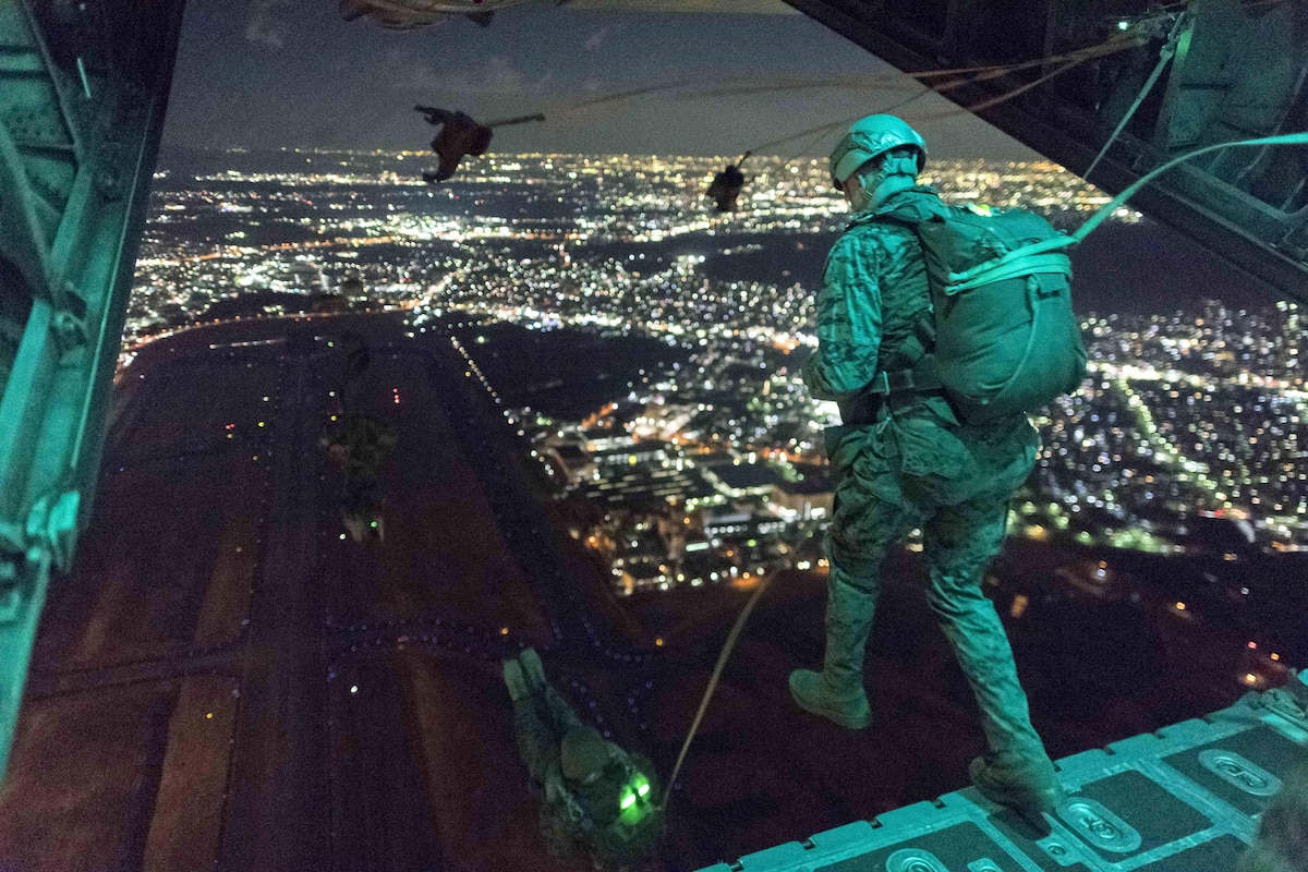 Marines jump from an aircraft at night with city lights in the distance.