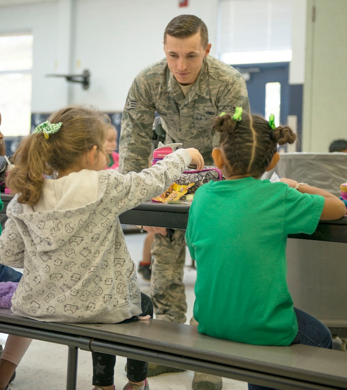 Staff Sgt. Justin Hogg, 96th Security Forces Squadron, visits with students about his new position over their lunch break Jan. 13 at Eglin Air Force Base, Fla.  Hogg is the School Resource Officer for Eglin Elementary School and is in charge of providing security and crime prevention services on the campus. (U.S. Air Force photo/Cheryl Sawyers)