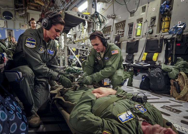 (Left) 1st Lt. Julia Lesage, a former first sergeant now flight nurse with the 315th Aeromedical Evacuation Squadron, and Senior Airman Josh Lykins, 315th AES medical technician, buckle in a simulated patient during a training mission aboard a C-17 Globemaster III en route to Ramstein Air Base Germany Jan. 13, 2016. (U.S. Air Force photo by Senior Airman Tom Brading)