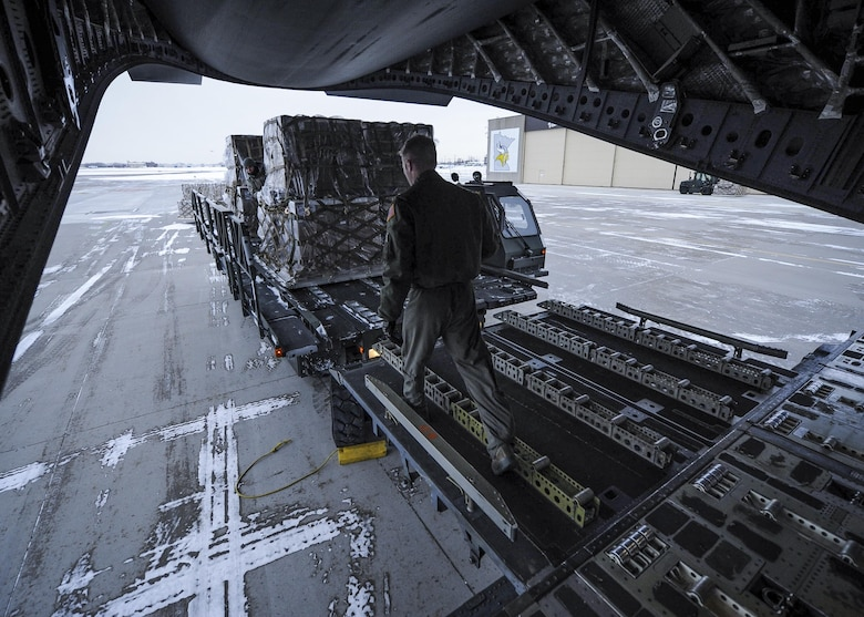 315th Airlift Wing loadmasters coordinate loading of humanitarian cargo onto a Joint Base Charleston C-17 Globemaster III Jan. 13, 2017 at Minneapolis-St. Paul Air Reserve Station, Minnesota.  The 315th AW hauled more than 50,000 pounds in donated meals to Ramstein Air Base, Germany. The cargo will be later delivered to refugees in northern Iraq. (U.S. Air Force photo by Senior Airman Tom Brading)