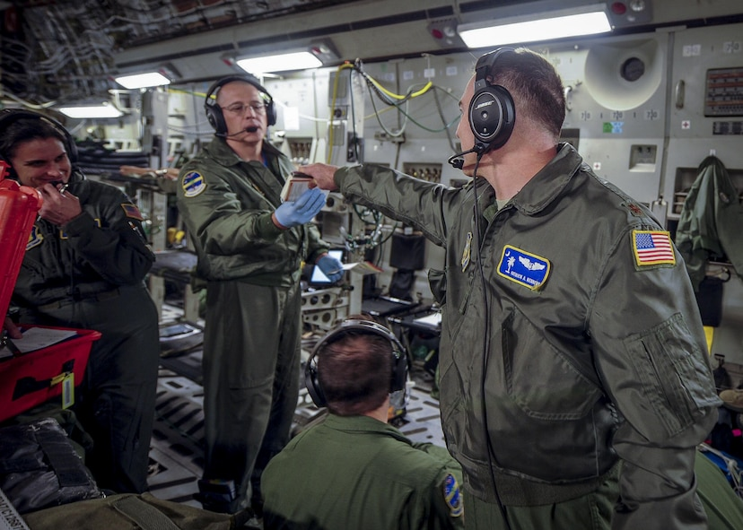 (From left) Maj. Patrick Kennedy, 315th Aeromedical Evacuation Squadron chief of standardizations and evaluations, hands a scenario card to Maj. Derek Stone, 315th AES, while conducting medical training Jan. 13, 2017, while on board a C-17 Globemaster III, bound for Ramstein Air Base, Germany. Each card contains various training emergencies for the medical professionals to overcome while in-flight. Airmen from the 315th AES are able to conduct medical training, while in conjunction with real-world operations. (U.S. Air Force photo by Senior Airman Tom Brading)