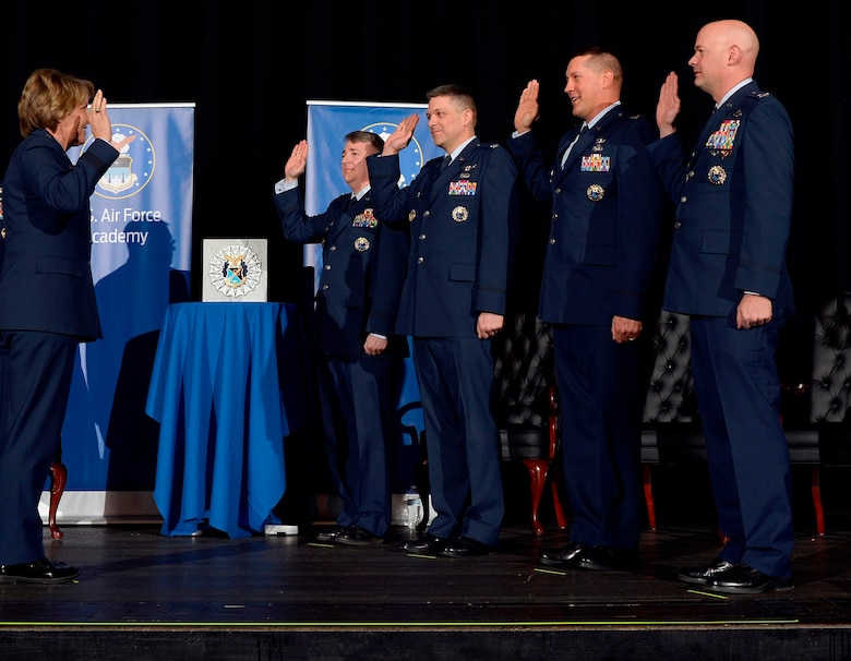 Lt. Gen. Michelle Johnson (left), the superintendent of the U.S. Air Force Academy, recognizes the Academy's four newest permanent professors at a Jan. 6, 2016 investiture ceremony in Arnold Hall. The professors are (from left to right): Col. John Cinnamon, head of the Aeronautics Department; Col. Scott Williams, head of the Mathematical Sciences Department; Col. Steven Hasstedt, head of the Biology Department; and Col. Mark Anarumo, director of the Center for Character and Leadership Development. (U.S. Air Force photo/Jason Gutierrez)