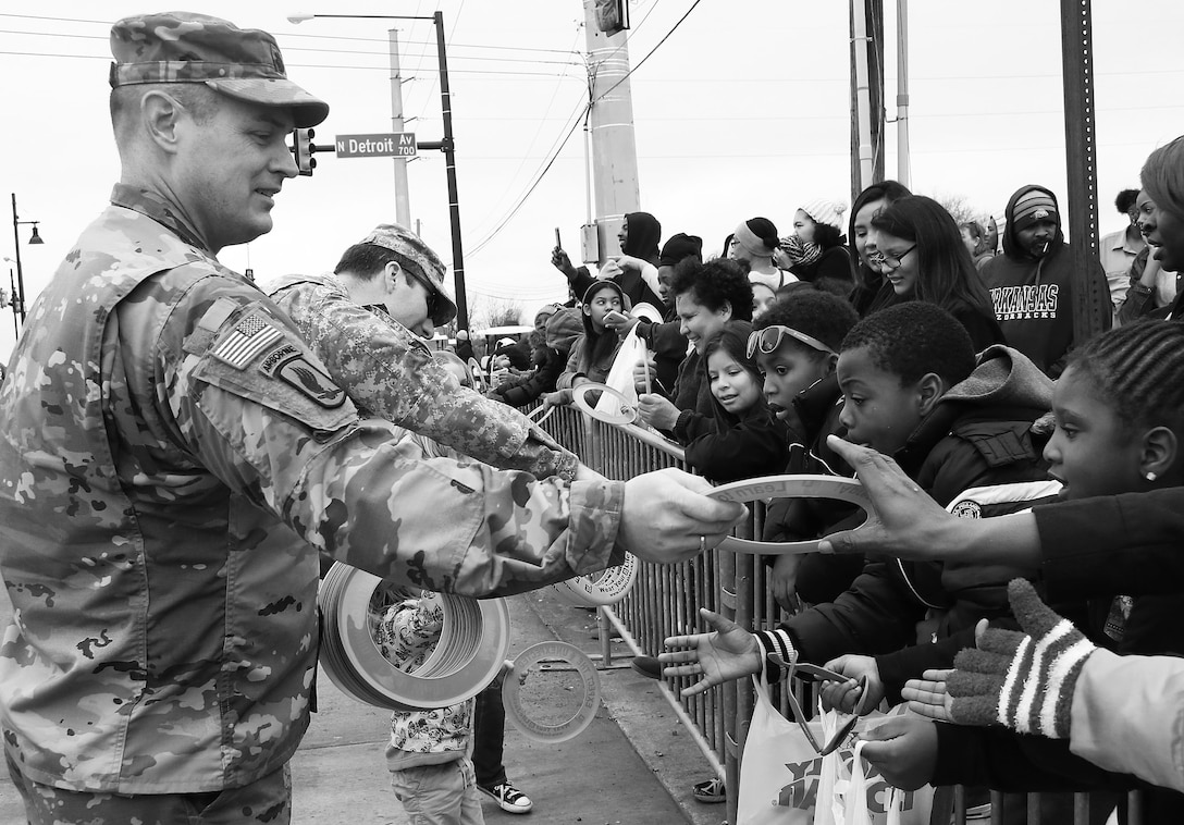 Lieutenant Colonel Dan Young, deputy commander, Tulsa District, U.S. Army Corps of Engineers, passes out frisbees as water safety reminders to children along the parade route at the 38th annual Martin Luther King Jr. Commemorative Parade in Tulsa, Okla., January 16, 2017.   Personnel from the Tulsa District have been participating in the city of Tulsa's MLK Day parade for more than 20 years. (U.S. Army Corps of Engineers photo by Preston Chasteen/Released)