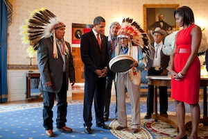 Presidential Medal of Freedom recipient Joseph Medicine Crow shows a drum to President Barack Obama and First Lady Michelle Obama during a reception for recipients and their families in the Blue Room of the White House on Aug. 12, 2009. (Official White House photo by Pete Souza)  P081209PS-0965