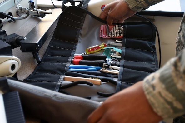 Senior Airman Donnell Johnson, 59th Medical Logistics and Readiness Squadron biomedical equipment technician, sifts through his tool kit during a Nov. 17 service call at the U.S. Air Force Post Graduate Dental School on Joint Base San Antonio-Lackland, Texas. The 59th MLRS BMET section is comprised of scheduled and unscheduled maintenance teams, initial inspectors, contracting services, quality assurance, information technology and technical assessment services. (U.S. Air Force photo/Staff Sgt. Jason Huddleston)