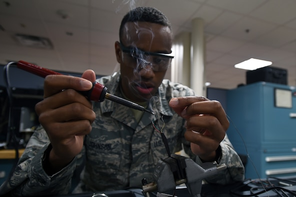 Senior Airman Donnell Johnson, 59th Medical Logistics and Readiness Squadron biomedical equipment technician, solders load cell wires Nov. 17 at the Wilford Hall Ambulatory Surgical Center on Joint Base San Antonio-Lackland, Texas. Load cells are used in electronic scales to measure weight and display the weight digitally. (U.S. Air Force photo/Staff Sgt. Jason Huddleston)