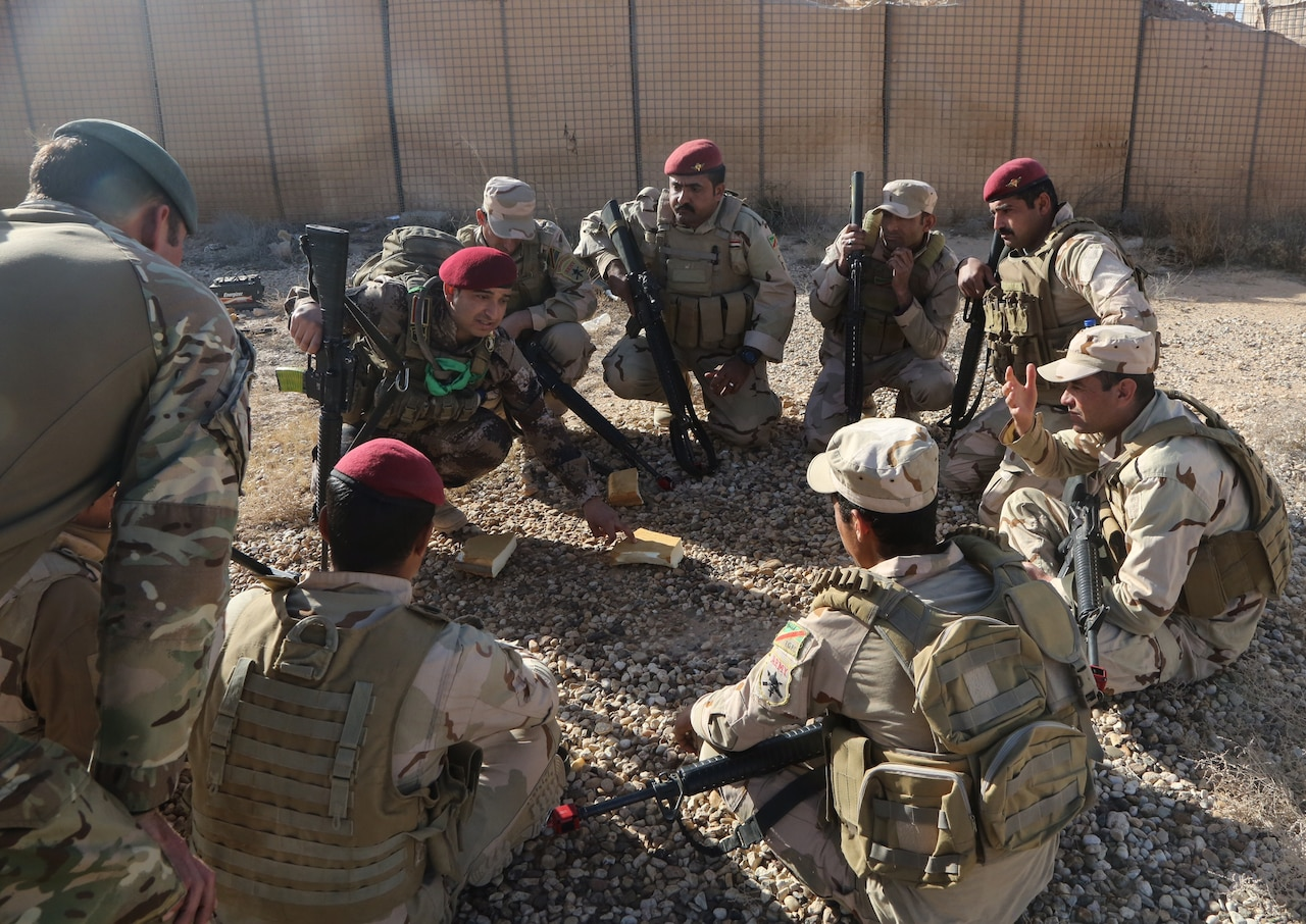 An Iraqi squad leader explains the squad movement tactics during assault movement training at Al Asad Air Base, Iraq, Jan. 13, 2017. Training at building-partner-capacity sites is an integral part of Combined Joint Task Force Operation Inherent Resolve's effort to train Iraqi security forces personnel to defeat the Islamic State of Iraq and the Levant. Army photo by Sgt. Lisa Soy