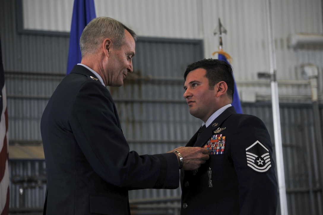 Lt. Gen. Darryl Roberson, (left) Air Education and Training Command commander, Joint Base San Antonio, Texas, presents Master Sgt. Gregory Gibbs, 512th Rescue Squadron operations superintendent, with the Distinguished Flying Cross medal at Kirtland Air Force Base, New Mexico, Jan. 13. Ranked as the highest military aviation award, Gibbs received the medal for distinguishing himself as a HH-60 Pave Hawk, aerial gunner in a high risk rescue mission in Afghanistan on May 26, 2011. Gibbs' split-second decision-making skills saved the lives of nine military members.