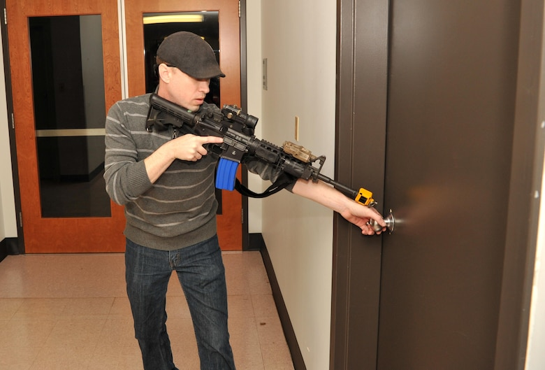 Staff Sgt. Chris Hall, a 9th Security Forces member, plays the role of an active shooter during an exercise Jan. 13, 2017 at Beale Air Force Base, California. The protocol during an active shooter scenario is to lock all doors and turn of lights in order to remain hidden. (U.S. Air Force photo/Airman Tristan D. Viglianco)