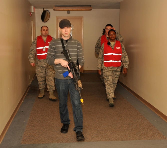 Staff Sgt. Chris Hall, 9th Security Forces member, plays the role of an active shooter and is followed by members of the Wing Inspection Team during an exercise Jan. 13, 2017 at Beale Air Force Base, California. The exercise took place without a majority of the base populous being informed ahead of time in order to better test the readiness of Team Beale. (U.S. Air Force photo/Airman Tristan D. Viglianco)