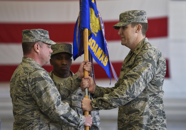 Col. Harry Seibert, commander of the 1st Special Operations Maintenance Group, presents Maj. Bryan Hogan, commander of the 801st Special Operations Aircraft Maintenance Squadron, with the 801st SOAMXS guidon during a change of command ceremony at Hurlburt Field, Fla., Jan. 12, 2017. Maj. Bryan Hogan took command of the 801st SOAMXS from outgoing commander, Lt. Col. Philip Broyles. (U.S. Air Force photo by Airman 1st Class Joseph Pick)