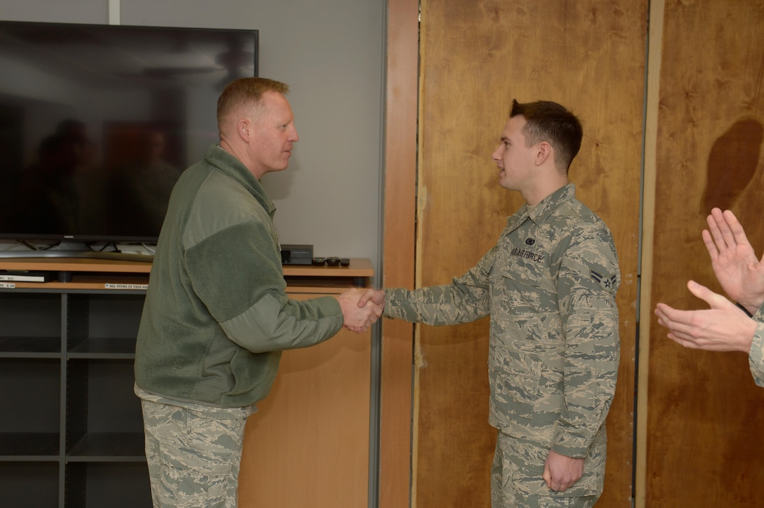 Airman 1st Class Ein Odgers, 52nd Logistics Readiness Squadron fuel distribution operator, is coined by Col. Joe McFall, 52nd Fighter Wing commander, for his actions in a Green Dot social experiment at Spangdahlem Air Base, Germany, Jan. 11, 2017. Green Dot has been conducting several scenarios around base to see how individuals will react to the actors. (U.S. Air Force photo by Staff Sgt. Jonathan Snyder)