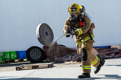 A 380th Expeditionary Civil Engineering Squadron firefighter throws a hose during a timed firefighter confidence course at an undisclosed location in Southwest Asia, Jan. 16, 2017. Wearing up to 75 pounds of equipment, participants completed nine stages during the course including a ladder climb, hose drag, sled pull, hose throw, equipment carry, forcible entry, hotel pack, equipment hoisting and rescue. (U.S. Air Force photo/Senior Airman Tyler Woodward)