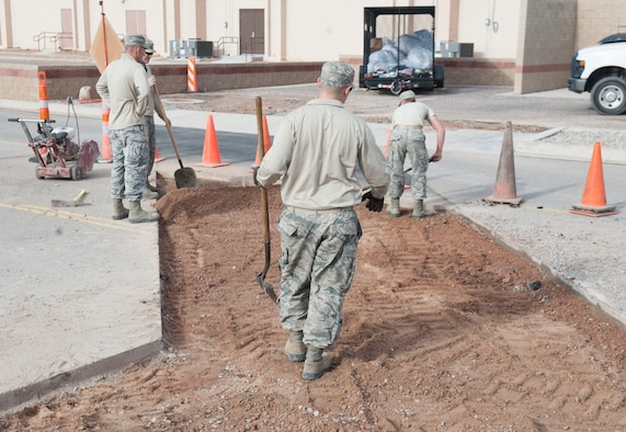 Pavement and Equipment craftsmen, assigned to the 49th Civil Engineer Squadron, level off soil in preparation to place fresh asphalt onto the roadway at Holloman Air Force Base, N.M., January 17, 2017. A utility break occurred under the roadway causing for the 49th CES to quickly respond and fix the problem. (U.S. Air Force photo by Airman Ilyana A. Escalona)