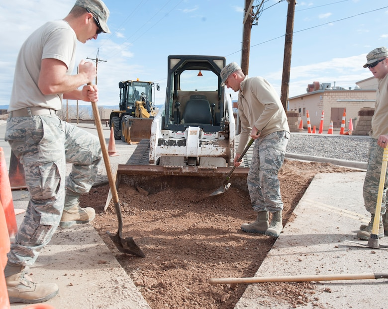 Staff Sgt. John Hoyt and Senior Airman Jordan Lechner, Pavement and Equipment craftsmen, assigned to the 49th Civil Engineer Squadron, shovel soil into a loader at Holloman Air Force Base, N.M., January 17, 2017. In order for asphalt to be placed onto the surface, the soil underneath it must be as smooth as possible. A utility break occurred under the roadway causing for the 49th CES to quickly respond and fix the problem. (U.S. Air Force photo by Airman Ilyana A. Escalona)