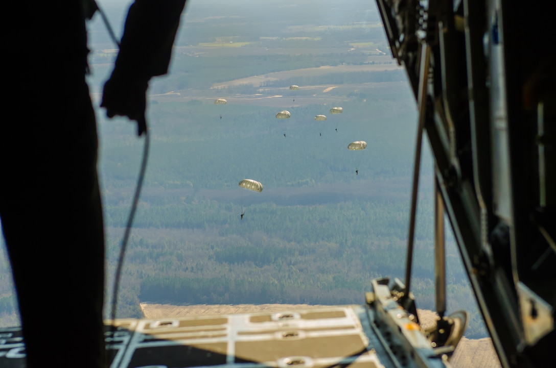 U.S. Soldiers assigned to the 421st Quartermaster Company, U.S. Army Reserve, perform a static line jump out of a C-130 Hercules belonging to the Missouri Air National Guard's 180th Airlift Squadron over Sylvania, Ga., on January 10, 2017.