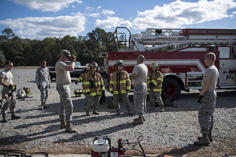 Members of an Emergency Medical Technician refresher course, listen to final instructions, during Vehicle Extrication training, Jan. 13, 2017, at Moody Air Force Base, Ga. The students donned the top half of the protective gear to shield them from any debris during the training. (U.S. Air Force photo by Airman 1st Class Janiqua P. Robinson)