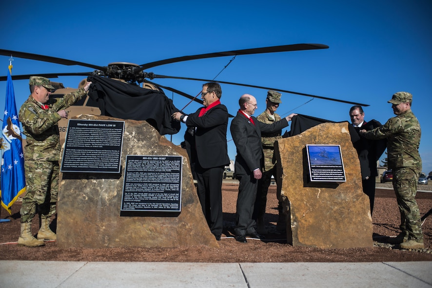 Attendees of a MH-53J Pave Low III dedication ceremony unveil plaques at the end of the ceremony Jan 17, 2017, at the air park on Cannon Air Force Base, N.M. The plaques describe the aircraft's history and mission accomplishments. (U.S. Air Force photo by Senior Airman Luke Kitterman/Released)