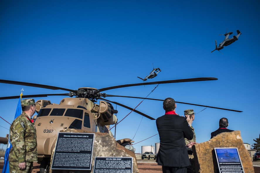 Attendees of a MH-53J Pave Low III dedication ceremony watch as two CV-22 Osprey aircraft conduct a flyover Jan 17, 2017, at the air park on Cannon Air Force Base, N.M. The flyover concluded the ceremony in which more than 150 people were in attendance. (U.S. Air Force photo by Senior Airman Luke Kitterman/Released)
