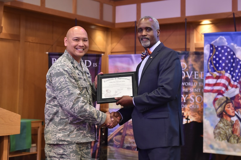 U.S. Air Force Col. Jimmy Canlas, 437 Airlift Wing commander, presents Melvin D. Willis, Space and Naval Warfare Systems Center – Atlantic Enterprise Information Systems Business manager, with a certificate of appreciation during the Dr. Martin Luther King Jr. remembrance event at the chapel Jan. 17, 2017 at Joint Base Charleston, South Carolina. Willis was the guest speaker for the ceremony honoring King's legacy. Willis is a former command chief master sergeant from the 437 Airlift Wing.