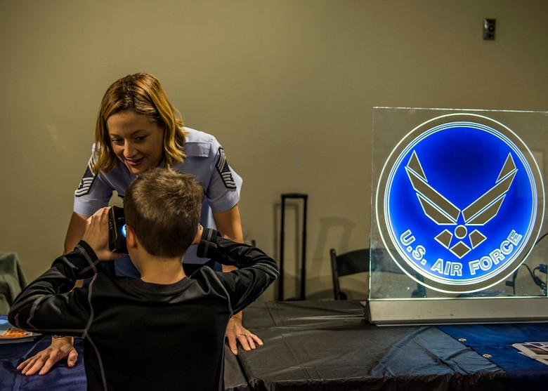 Chief Master Sgt. Diane Slazinik, 375th Communications Group superintendent, asks a visitor what they're experiencing while they use the Google cardboard virtual reality box to see what it looks like to jump out of a plane as a paratrooper. (U.S. Air Force photo by Staff Sgt. Jodi Martinez)