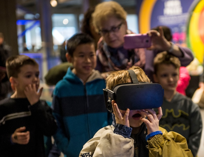 A child reacts while having a virtual reality experience at the Air Force booth.  (U.S. Air Force photo by Staff Sgt. Jodi Martinez)