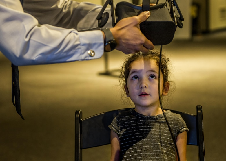 Staff Sgt. Charles Quinsay, helps a visitor adjust the virtual reality headset. (U.S. Air Force photo by Staff Sgt. Jodi Martinez)