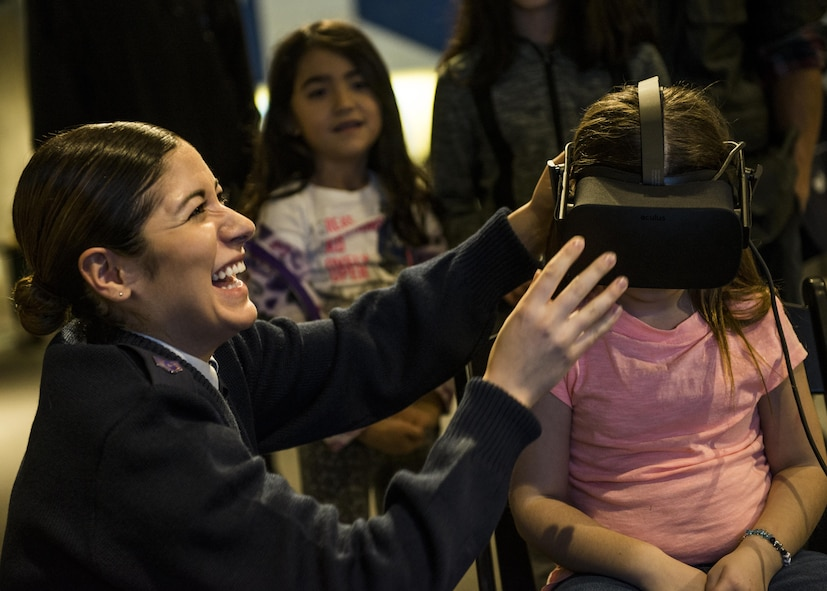 Staff Sgt. Merissa Hunnicut, 345th Recruiting Squadron recruiter, laughs as she helps a visitor put on the virtual reality headset. (U.S. Air Force photo by Staff Sgt. Jodi Martinez)