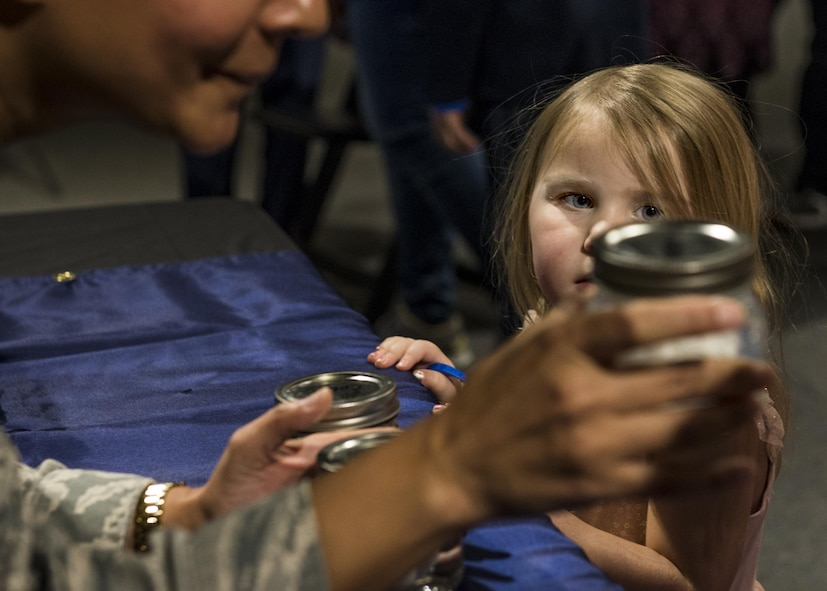 A girl looks at a jar that Maj. Anita Shade, 375th Dental Squadron residency director, holds to show the effects of acid on teeth during the event. (U.S. Air Force photo by Staff Sgt. Jodi Martinez)