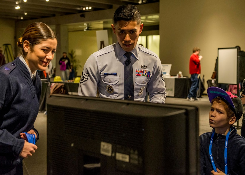Staff Sgt. Merissa Hunnicut, 345th Recruiting Squadron recruiter, and Staff Sgt. Charles Quinsay, prepare a system for a virtual reality experience during the event.  (U.S. Air Force photo by Staff Sgt. Jodi Martinez)
