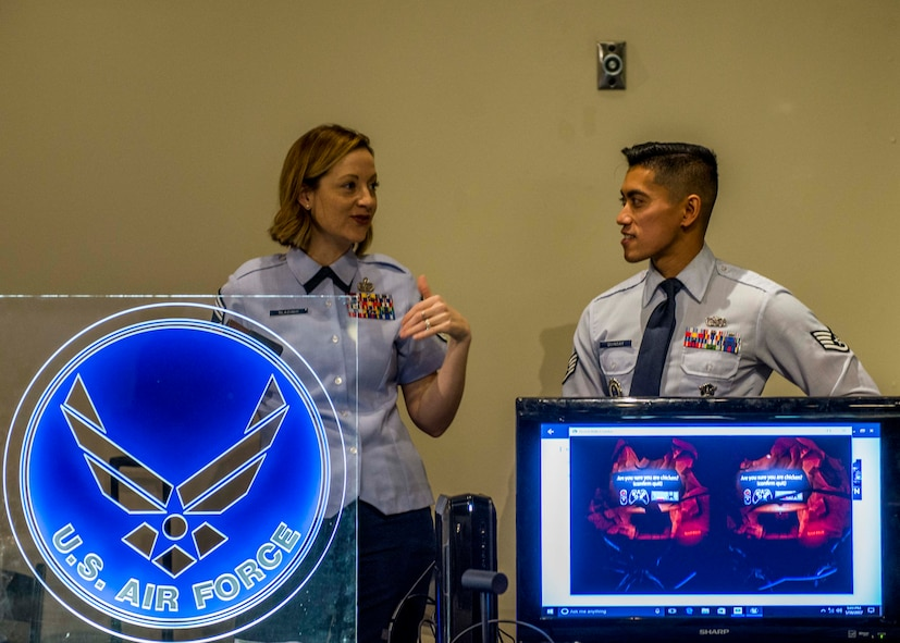 Chief Master Sgt. Diane Slazinik, 375th Communications Group superintendent, and Staff Sgt. Charles Quinsay, talk during the event next to the Air Force logo and the virtual reality screen.  (U.S. Air Force photo by Staff Sgt. Jodi Martinez)
