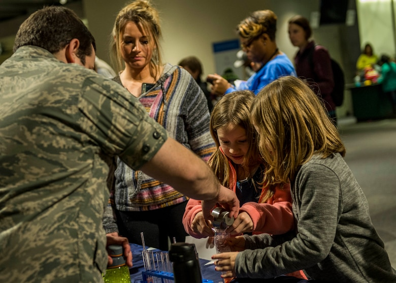 Capt. Nicholas Littman, 375th Aerospace Medicine Squadron, teaches two young girls how to extract DNA from a strawberry. (U.S. Air Force photo by Staff Sgt. Jodi Martinez) (U.S. Air Force photo by Staff Sgt. Jodi Martinez)