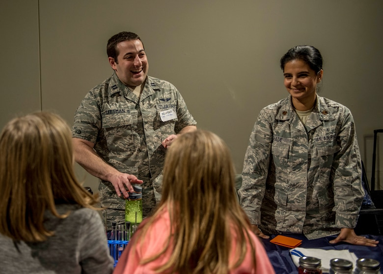 Capt. Nicholas Littman, 375th Aerospace Medicine Squadron, and Maj. Anita Shade, 375th Dental Squadron residency director, teach two young girls about the effects that acid has on teeth during the event. (U.S. Air Force photo by Staff Sgt. Jodi Martinez)