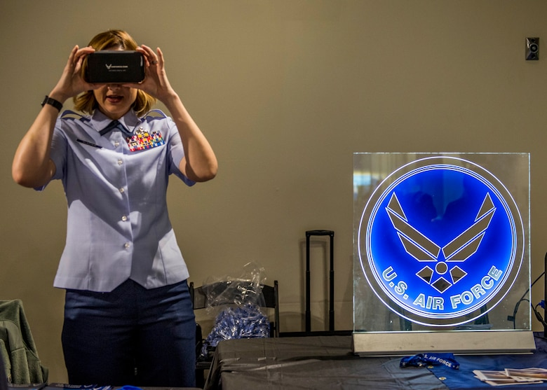 Chief Master Sgt. Diane Slazinik, 375th Communications Group superintendent, prepares the Google cardboard virtual reality for a paratrooper experience. (U.S. Air Force photo by Staff Sgt. Jodi Martinez)