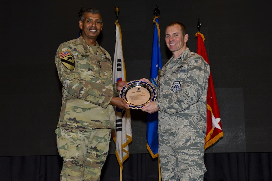 U.S. Air Force Col. Cary Culbertson, 51st Fighter Wing vice commander, presents U.S. Army Gen. Vincent K. Brookes, United States Forces Korea commander, with a token of appreciation at Osan Air Base, Republic of Korea, Jan. 16, 2017. Brooks was the keynote speaker at the Osan Martin Luther King Jr. Day memorial program and presented several members of Team Osan with awards in recognition of their contributions to making the Osan community better. (U.S. Air Force photo by Senior Airman Victor J. Caputo)