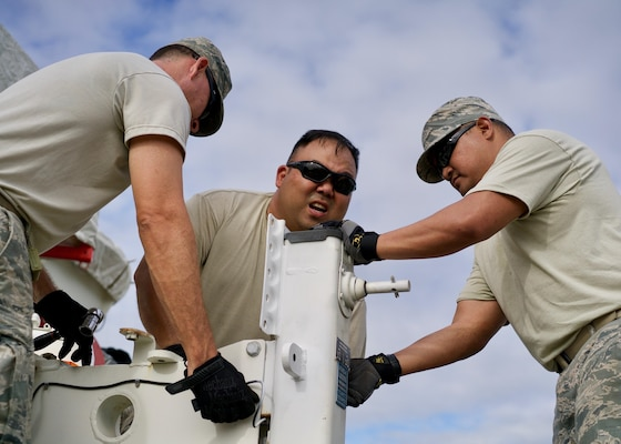 Air Force Master Sgt. Eric Martin (left), Tech. Sgt. Kyle Kikuchi (center) and Staff Sgt. Joel Fernandez (right), level a downlink antenna, Clark Air Base, Philippines, Jan. 15, 2017. Martin, Kikuchi and Fernandez are Eagle Vision team members who are deployed to the Philippines to support a Pacific Air Forces Subject Matter Expert Exchange mission. The team will work with Philippine Airmen to share how satellite imagery can help enhance Humanitarian Assistance and Disaster Relief efforts common in the Asia-Pacific.(U.S. Air Force photo by Tech. Sgt. James Stewart/Released)